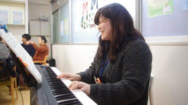 オレンジリングをつけてピアノを演奏する学生